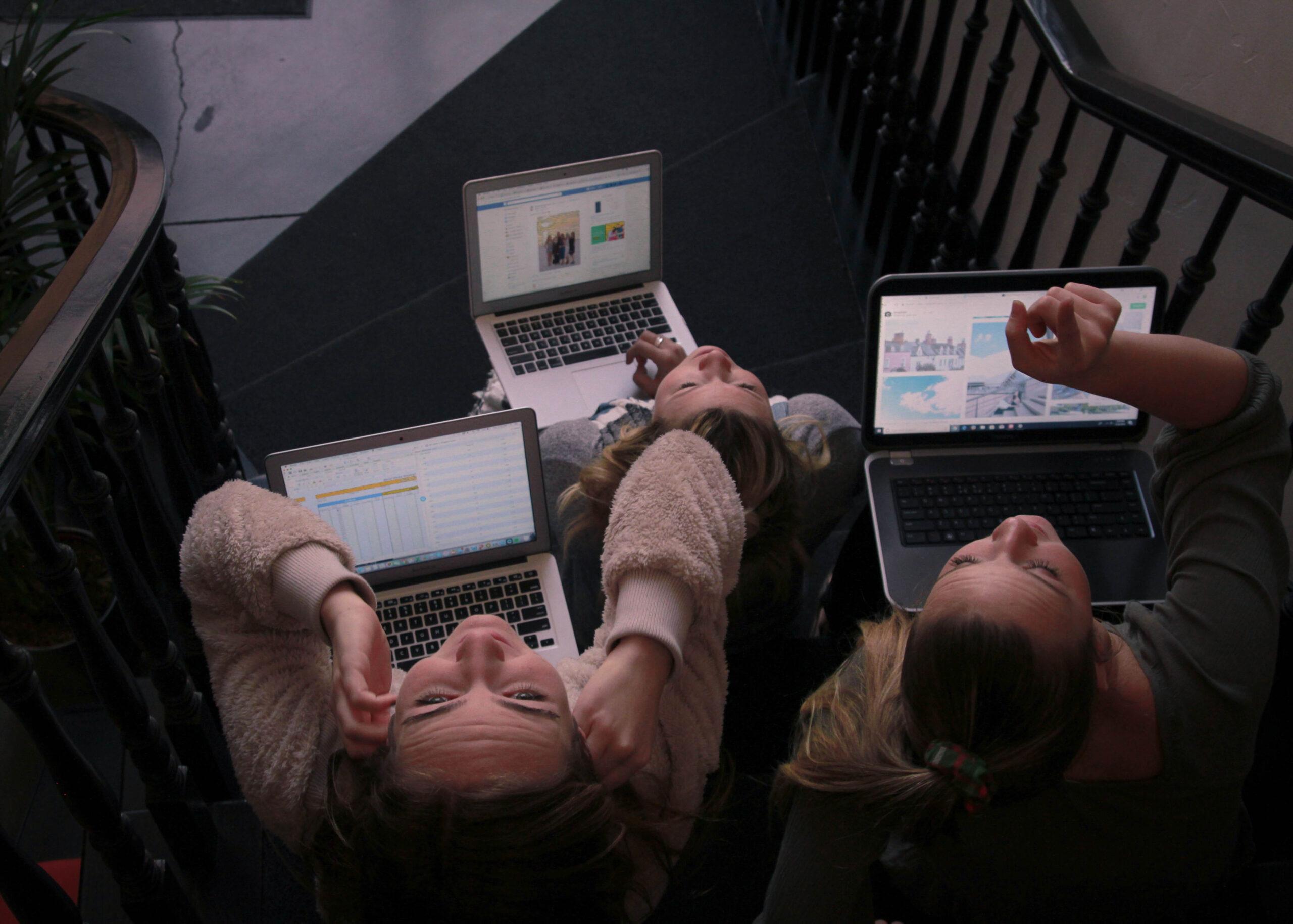 Symbolbild mit drei Mädchen mit einem Laptop, die nach oben schauen.